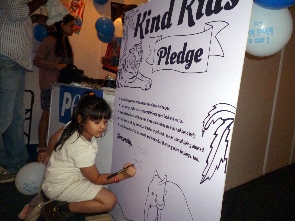 Kids signing the petition at PETA stall in IKFW