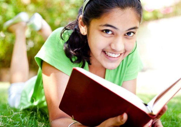 Cheerful Casual Indian Teenage Girl Lying on Front Reading Book